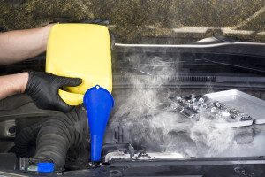 A mechanic pours engine coolant into an overheated automobile ra