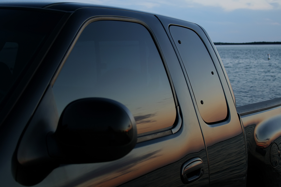 American black truck parked at the beach with a sunset reflection in the tinted window