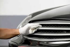 Car Chrome Polish with white gloves on front of car