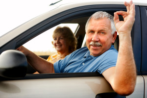 Smiling happy elderly couple in the new car